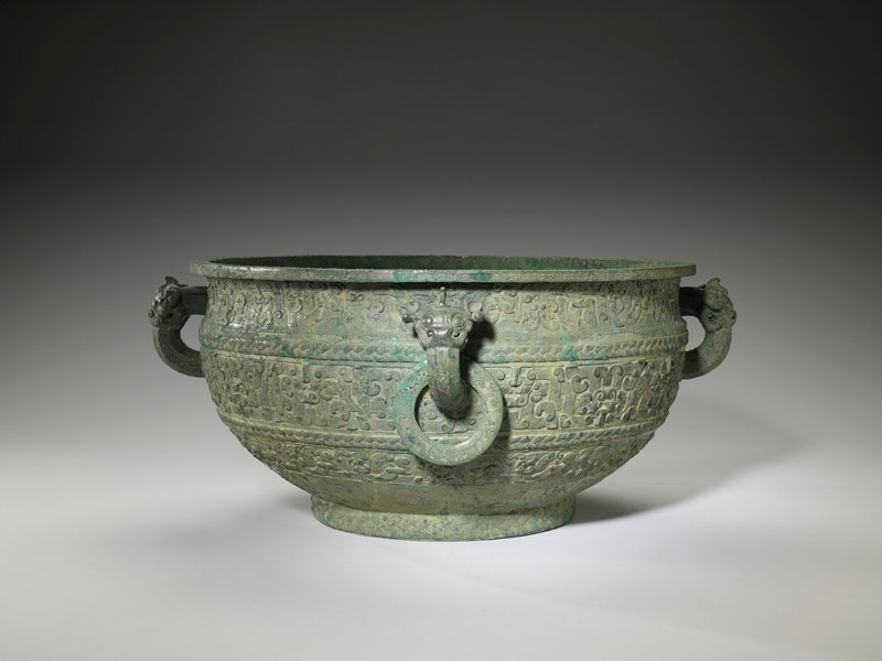 The shape of this vessel, called a Kien in its inscription, is very like that of the earlier Kuei. Fundamentally a Kien was a basin for holding water, but it is more probable that this example was not a profane vessel, but a ritual one. A companion vessel, exactly like this one and with the same inscription, is in the Freer Gallery. The decor is desposed in three belts separated by bands of plait-pattern, each strand in the plait made up of a number of very thin threads. A similar plait appears on the foot rim. The neck rim is adorned with a narrow band of cowries. The top and bottom belts on the body carry interlaced dragons, the head of every second one being close to the lower margin, the intervening heads being close to the upper. In the broad central belt are t'ao-t'ieh heads, every second seen right as the vessel stands, the intervening ones seen from above. This intricate scheme of interlaced bodies is clearly to be seen in Karlgren, number 51, figures 53 and 54. The four stout handles have t'ao-t'ieh heads at the top. This creature, with broad rolled up nose and a protruding, hooked crest in place of the ancient forehead sheild, is very different from the early ogre head. A row of stylized cicadas adorns the front and sides of the handles, and there are interlaced dragons on the flat, movable rings suspended from two of the handles. The technical execution of these decor elements narrow bare borders to every band, the center filled with either spirals or volutes with triangles, is exceedingly close to that on vessels of the Li-yu find (Umehara, Etude, plates 1 ff.) This is particularly interesting since Li-yu is in northern Shansi and the present vessels, according to Jung Keng (Shang-Chou, Volume 1, Page 470), were found in Huei-hien in northern Honan, thus both belong to the northern sphere. C.F. Yau suggests Kin-ts'un as the locale of this basin. Patina Light green with patches of blue. The inscription reads 'Kien-vessel [to be] handled [i.e. used] by the nobleman Chi.' For a discussion of the inscript