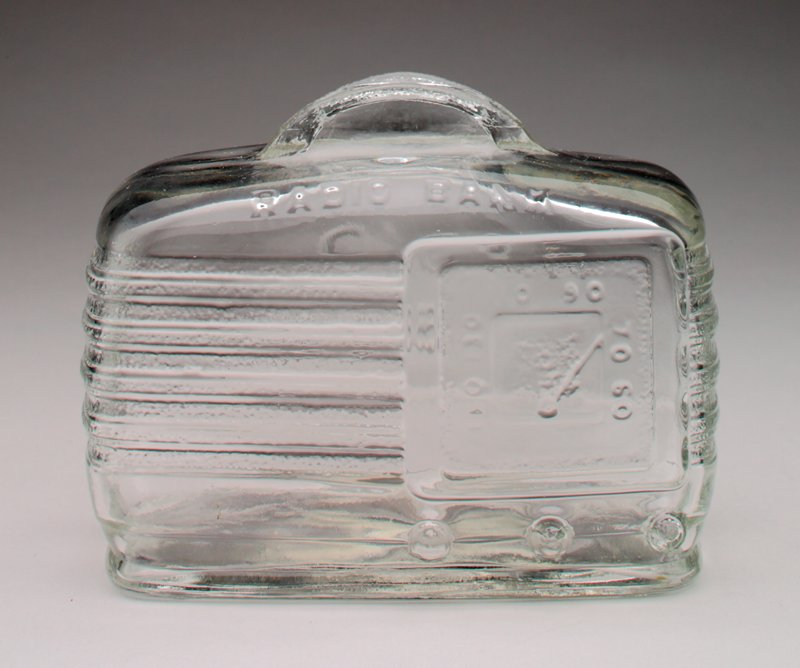 clear glass; moulded in the shape of a radio; raised coin slot on top