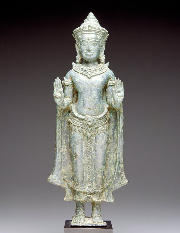 standing Buddha wearing cape; both hands raised in abaya mudra; wearing caplike crown, earrings and necklace; attached to mount