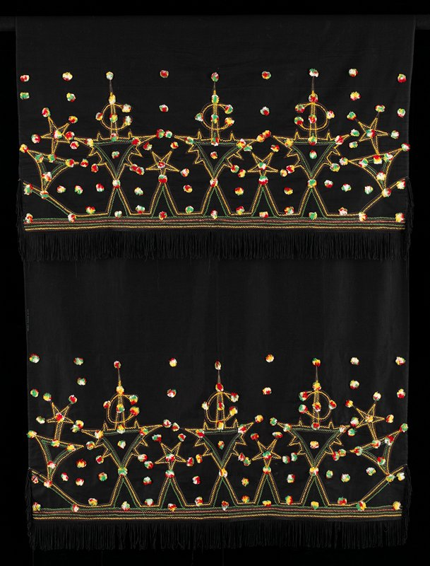 black; black fringe at short ends and corners; embroidery on ends on opposite sides in yellow, green, red, salmon and white in diamonds, stars and c-shapes with flattened pompoms