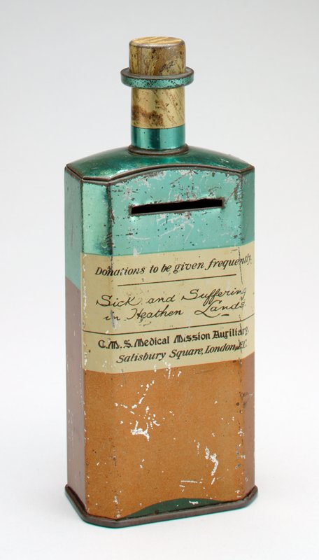 "bottle-shaped with ""cork"" stopper; brown ""medicine"" inside a green ""bottle""; yellow label: ""Donation to be given frequently. / Sick and Suffering in Heathen Lands. / C.M.S. Medical Mission Auxiliary, / Salisbury Square, London, E.C."""