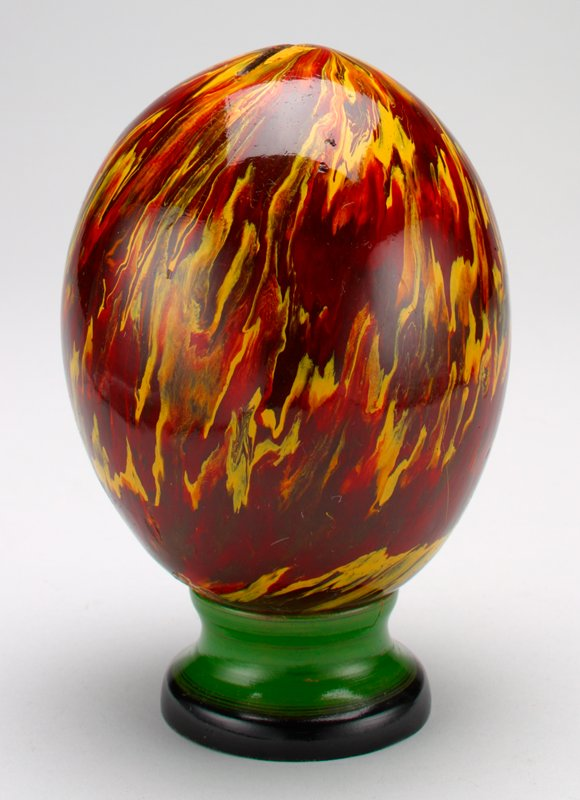 egg-shaped bank; painted red and yellow with green and black pedestal (removable)