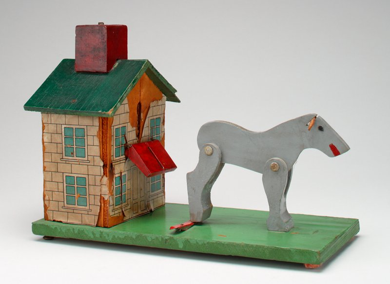 grey mule with leather ears and hind legs up; house with paper siding, green roof and red chimney attached to a green board; felt pads on bottom