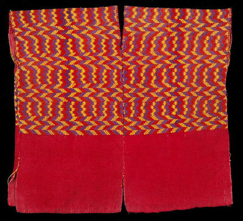 Shoulder area has supplementary weft patterning consisting of bands of arrows and waves in yellow, purple, red; plain red to the waist.