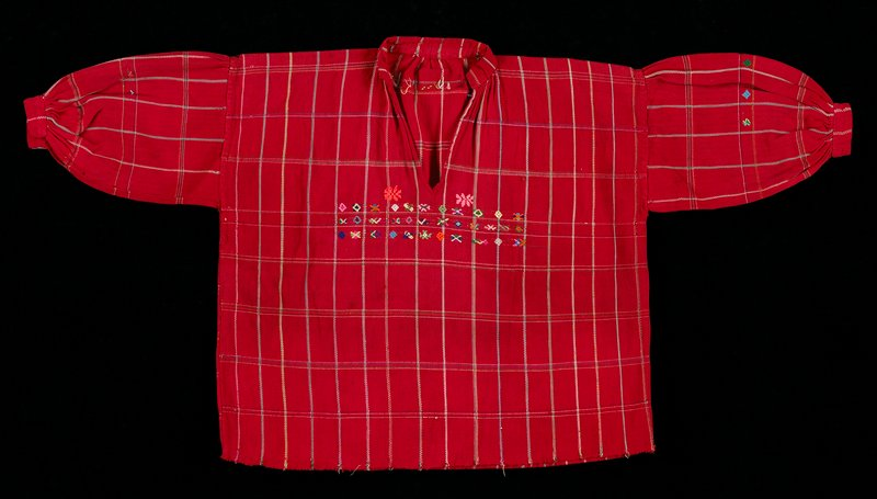 Red shirt with v-neck and collar; red background with lined multicolored rectangular checks; geometric designs on chest, sleeves and shoulders.