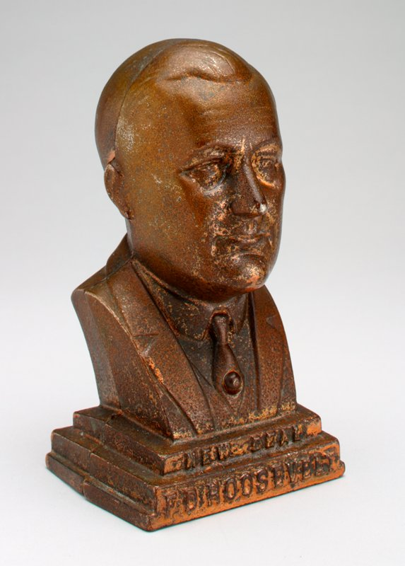 "bust of FDR on a stepped base; ""New Deal, F D Roosevelt"" in raised letters at bottom front; copper patina"