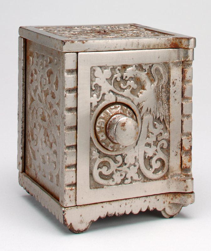 "square silver bank safe with numeric combination knob at left center on door; ""saving bank"" at top surrounded by raised vine design; scrollwork at sides; coin slot at top back panel; 12 large holes drilled in base to see contents"