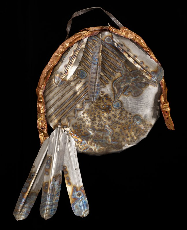 "round shield-shape; six ""feathers"" attached to shield; twisted hanging loop; two copper elements hang over top; burnished designs including bird and sun on shield and feathers"