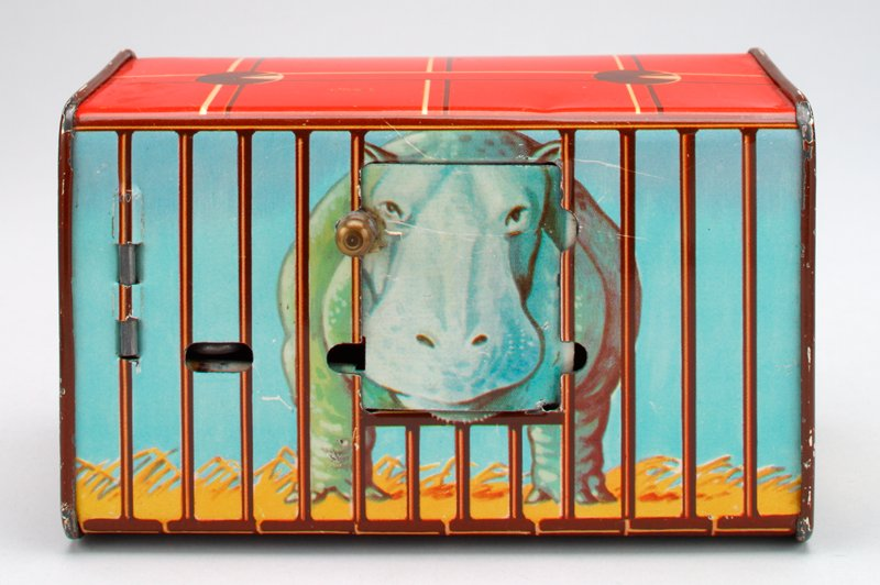 rectangular bank; metal folds secure together at short ends; caged hippopotamus whose face and backside can be seen on opposite long sides; a knob at the front slides a panel sticking the hippo's tongue out, trigger mechanism closes it; keyed door at right side