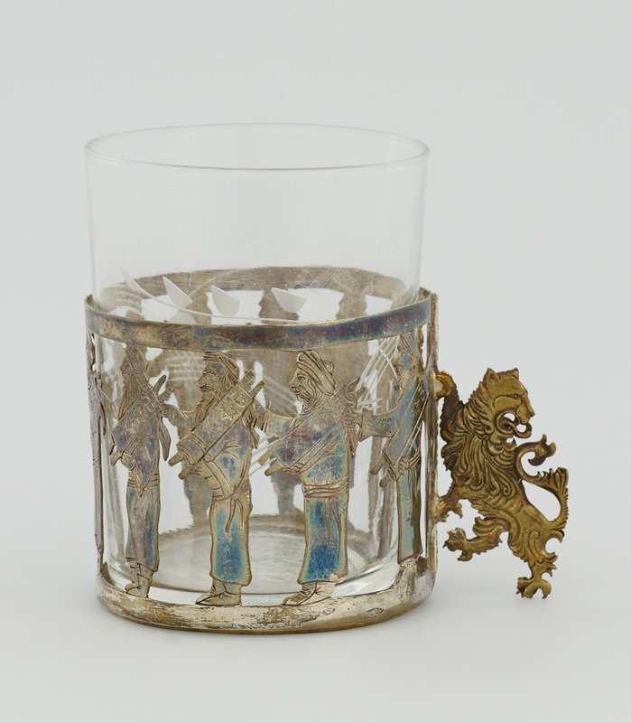 "clear glass tumbler with cut leaf and branch designs; metal sleeve for cup has lion ""handle""; openwork design of 10 standing men holding torahs"