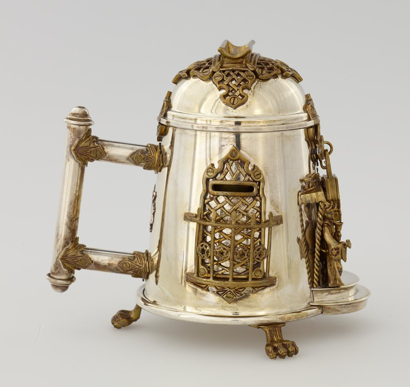 "roughly stein-shaped, with handle in back; 3 lion's paw feet; male and female figures on front flank a small door with small canopy; lock hangs between figures; railing-fronted ""window""-coin slots on sides; 3 keys (2 with birds- one silver, one gold and silver key with star); gold padlock"
