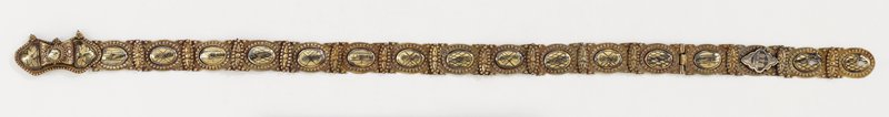 brass links with nailhead designs and central cartouche with designs in black; buckle decorated in floral motif