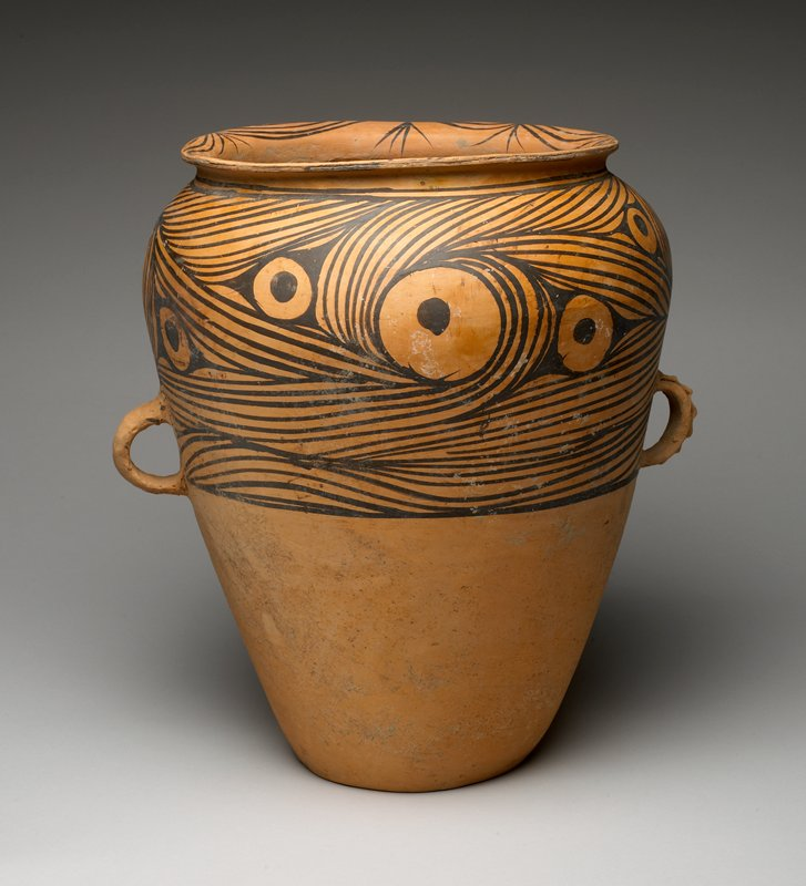 vessel on flat foot, flaring outward to shoulder and inward to wide, outward-turned mouth; pair of decorative loop handles, one with applied loop design; black painted decoration of curved lines and eyeball-like circles