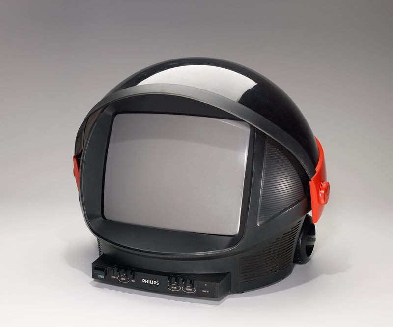 "rounded body with a flip-top ""visor""; entire unit resembles a helmet; black with red; wheels on back"