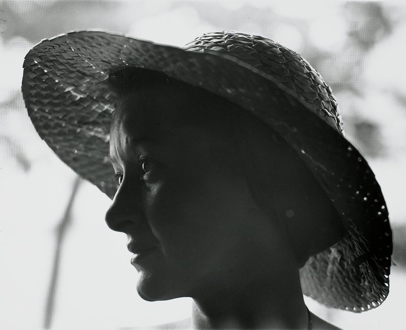 head of woman wearing straw hat, with head turned to PR