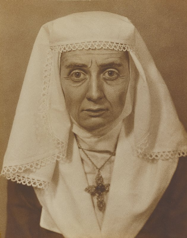 head and shoulders of a woman wearing a white head kerchief and large crucifix over a white collar; very large eyes