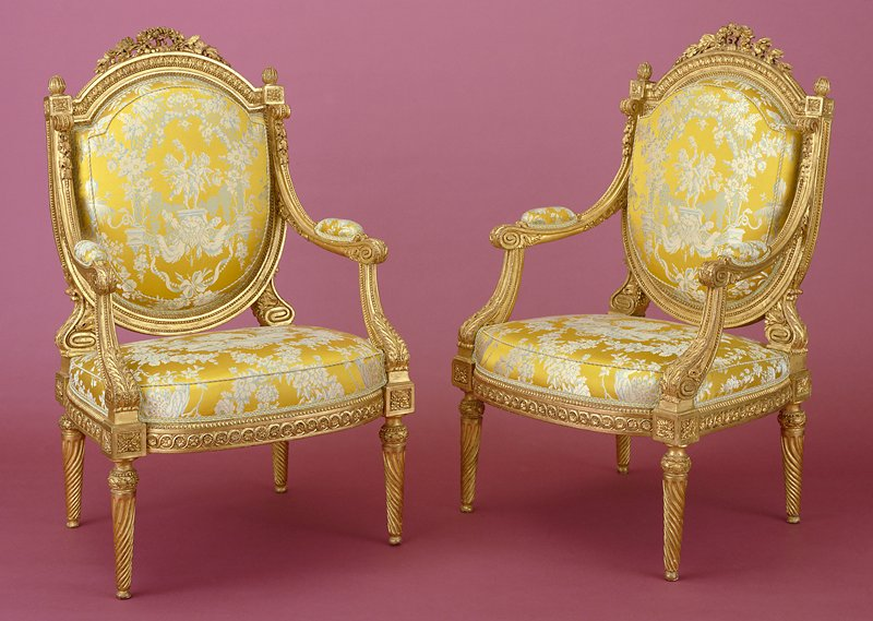 One of a set of four arm chairs (fauteuil) with flat sheild shaped backs in carved and gilded wood. Top of back decorated with carved oak leaves, garlands, ribbons, acanthus leaves, interlaces and laurel leaves. Legs with twisted grooves. Traces of old labels and cachets of red wax. Upholstery in yellow silk, blue and cream designs of cupids, animals,leaves and draperies.