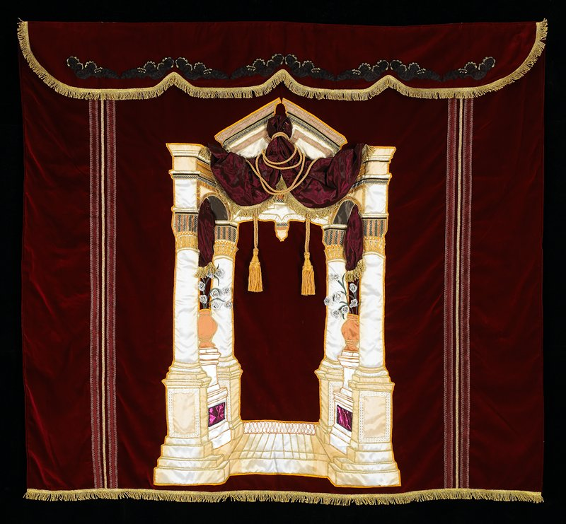 dark red velvet curtain with heavy gold fringe; central applique arch with heavy swag with tassels; pair of urns with silver flowers; thick gold embroidery and trim