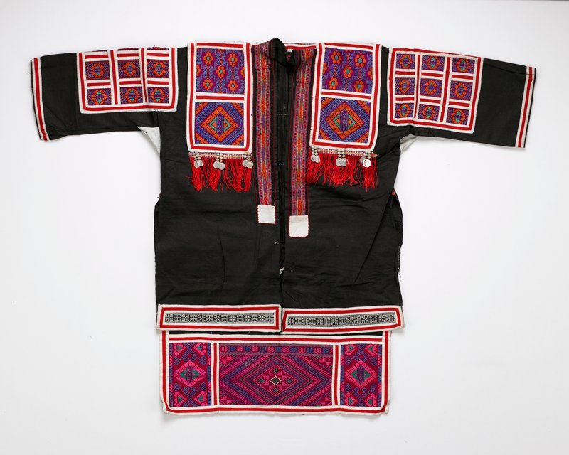black body; long tails in front; fuscha, orange, green and blue embriodered panels on chest, arms and back; red and white applique trim; red synthetic fringe with seed or bean and coin trim