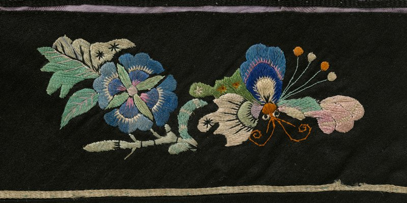 purple silk; blue lining; blue striped waistband; black cuffs embroidered with insects and flowers