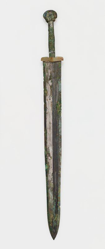 There is a narrow bevel on the cutting edges of this weapon and a ridge extending from the top to the point in the center of the blade. The hilt is slender and oblong in cross section. The pommel, in the form of a crouching animal, has a spiral decor in gold and silver thread inlay. Patina green and bluish-green with areas of acid green. Bronze with gold and silver inlay.