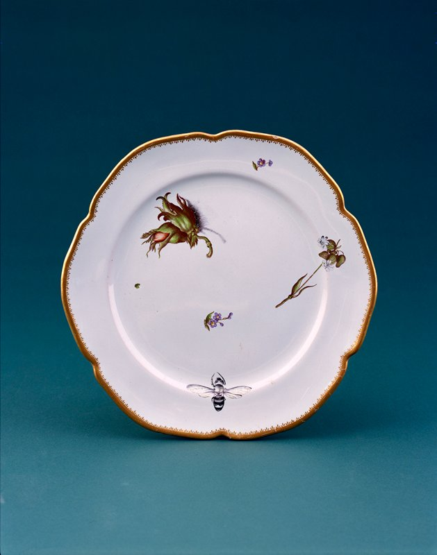 six lobed faience plate with scattered floral decorations and a bee with open wings in various colors; gold border
