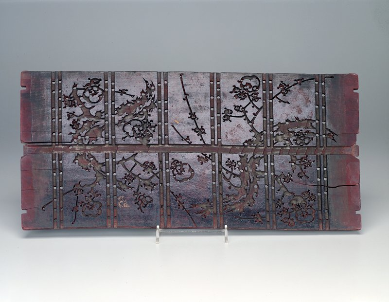 three rectangular panels carved with organic design moving between each panel; holes drilled through at important points with channels connecting each at back; six double bands at front