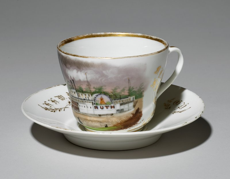 "cup decorated with painted design of steamboat ""Ruth""; 4 figures on boat; 4 figures on shore, one fishing; gold leaf sprays, text and gold edging at foot, rim, heandle and interior bottom; saucer decorated with gold leaf sprays, rims and initials"