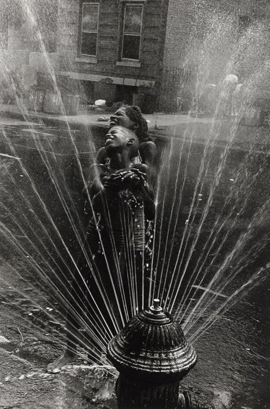 spraying fire hydrant at bottom center; boy standing in front of a girl, with their heads up and turned to PR, away from spray