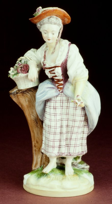 faience figure of a woman standing bare-foot on grassy mound in chintz-like peasant clothes; she leans on a tree stump, over her right arm a flower basket and in her left hand a large blossom; refined in shape and painting, these figures are much more delicate than those seen at Strasbourg during the same period
