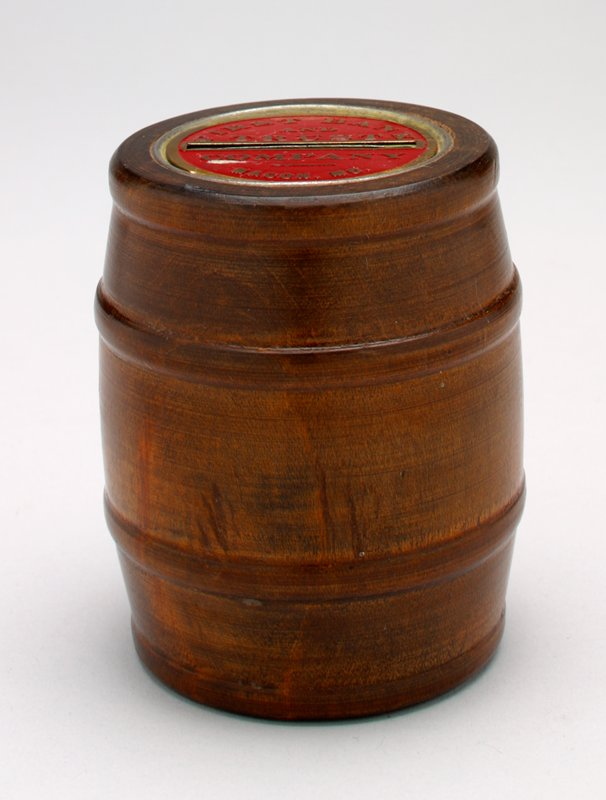wooden barrel; metal top and bottom are brass-colored with red