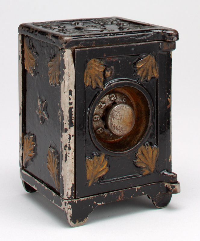 combination safe with dial at center of front door; stars, moon and fronds on top, stars and fronds on sides; black and gold
