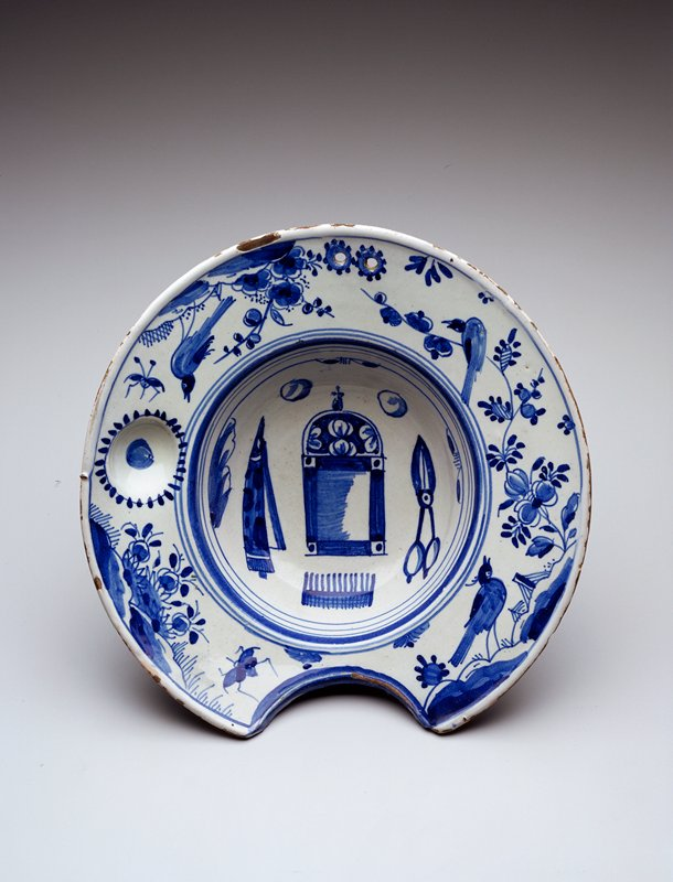 blue and white design; birds around rim; scissors, razor, comb and mirror images inside basin; rim indent for neck