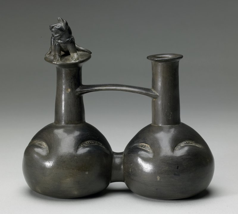 two bulbous chambers with long necks; necks connected with handle; one neck topped with partially reclining cat; other neck has flat ring mouth; four crescent-shaped indenations on each chamber; dark patina
