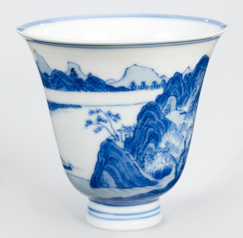 blue and white Imperial porcelain; inverted bell shape; continuous landscape scene of mountainous river landscape with houses obscured behind willow on surface; medallion of a single fisherman beside a cliff at center of the interior