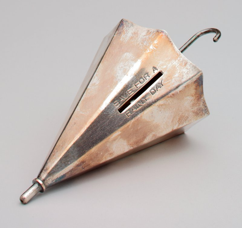silver, partially unfurled umbrella with a cane shaped handle; a coin slot on the top has the words[save for a rainy day] above and below stamped into it;