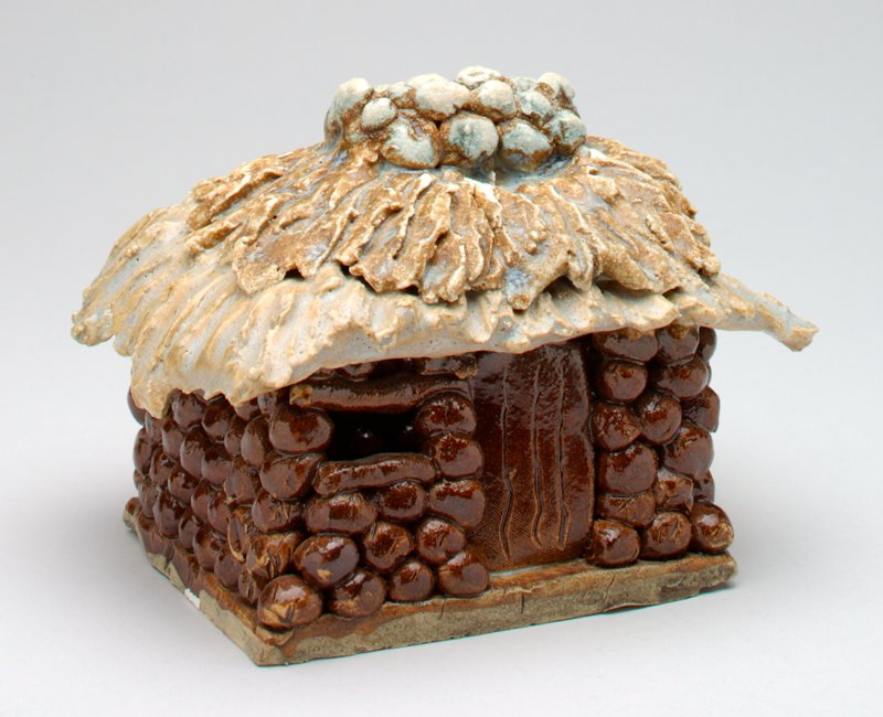ceramic building; brown balls form walls; tan/beige grass roof; stone chimney; chimney is coin slot; window could be used for small coins;