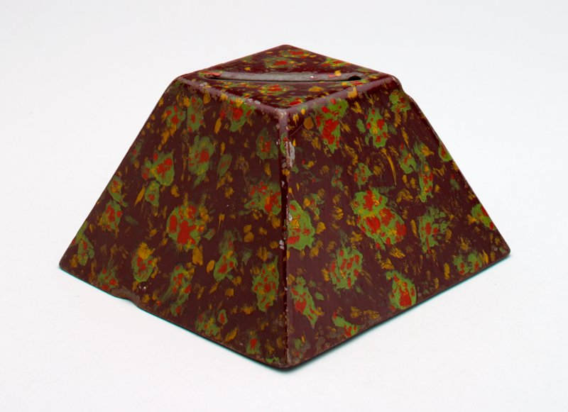 brown metal pyramid with flat top; red, green and gold abstract designs painted overall; coin slot in top