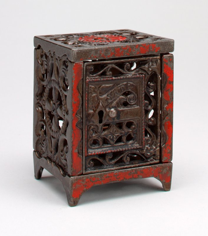 brown safe; open work sides, top and perforated bottom; red pigment on front and floral motif on top; scroll and leaf motifs form open work