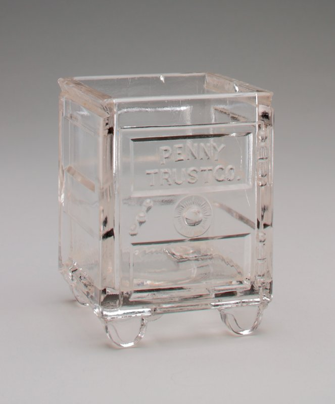 clear glass safe standing on 4 small legs; on front above handle and dial: 'Penny Trust Co.' in raised letters
