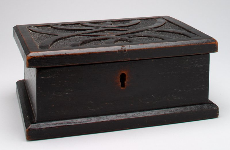 black wood rectangular box with carved lid; coin slot on top; keyhole on front; bottom is screwed on; hinges at back of lid
