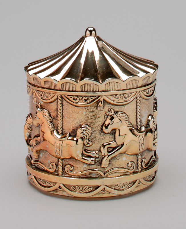 gold colored metal merry-go-round with 5 prancing horses on poles; tent shaped top; scallop above and below; felt pad on bottom