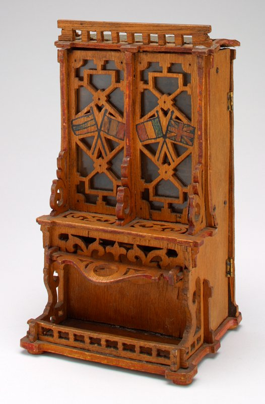 carved tall chest or hutch with glass doors; flags painted on wood portions of doors; traces of red paint on edges of doors, top, bottom; back is hinged and opens