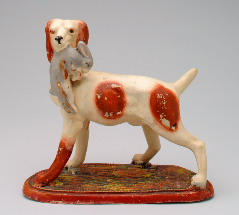 standing ceramic tan and liver colored dog holding a grey rabbit in its mouth; docked tail and long ears; coin slot back of neck; standing on a black, green and red and gold base