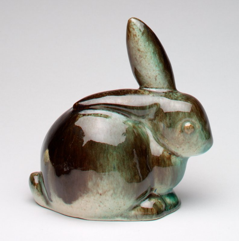 brown/green mottled ceramic bunny; one ear up, one down; coin slot adjacent to down ear