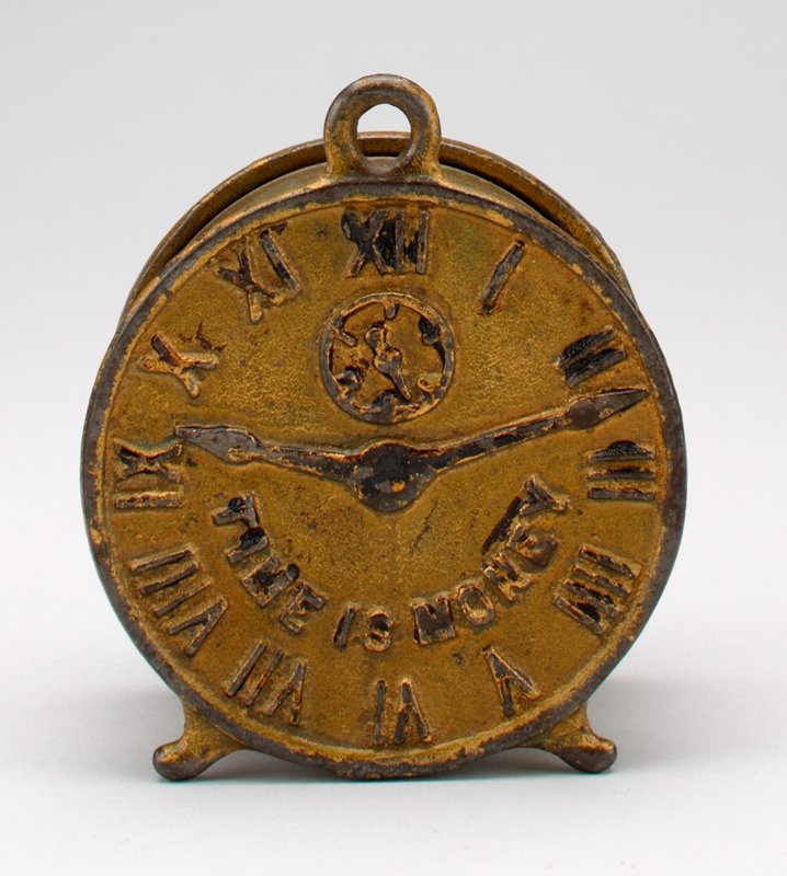 gold clock face with Roman numerals; traces of black pigment on hands and around some numbers; coin slot in back