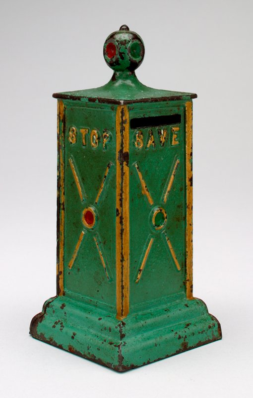 """green metal rectangular shaped traffic light with """"Stop"""" and a red light on 2 sides and """"Save"""" with a green light on 2 sides; the bank is trimmed in gold pigment; in 2 parts held together by a screw; there is a coin slot on both on the 2 """"Save"""" sides"""