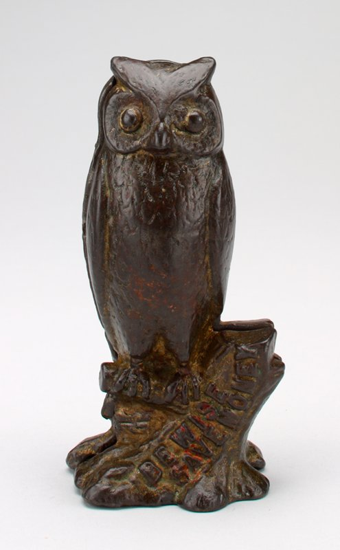 brown metal owl seated on tree stump; traces of gold and red pigment; coin slot in back of head