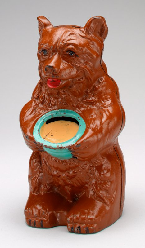 brown bear holding blue bowl filled with honey(?); black eyes, red tongue; coin slot at back of bowl
