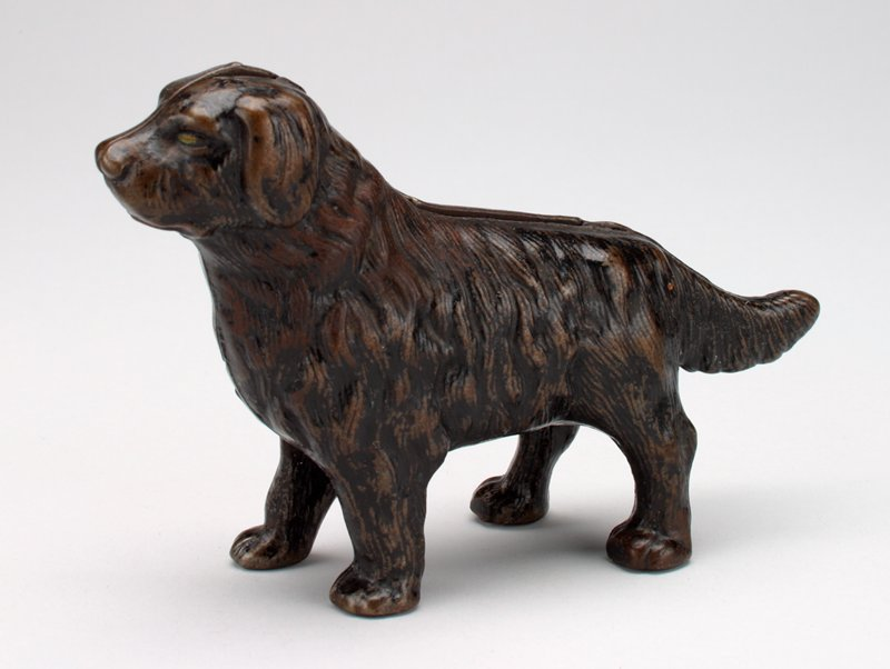 brown and black dog, long hair and tail; coin slot in back; red mouth